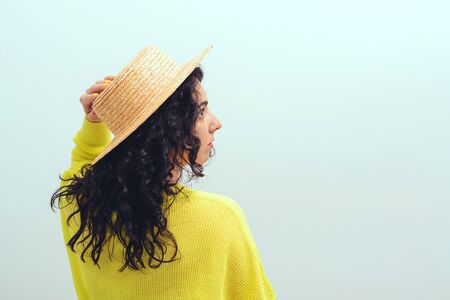 Brunette girl with long curly hair. Pretty woman wears hat and yellow pullover. Beauty and fashion. Healthy lifestyle, wellness. Profile of fashionable woman, over blue background. Copy space. Banque d'images