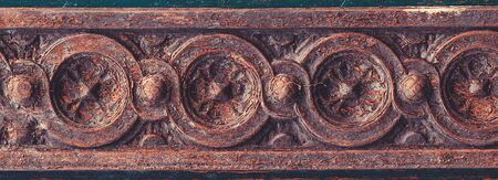 Old patterns on a wooden door. Wooden carving gate. Vintage textures and details on doorway. Woodcarving of the entrance door. Banque d'images