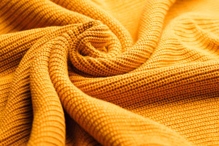 Orange textile background knitwear. Wool background, top view. Abstract fresh colorful yellow knitted pattern background texture. Orange knitted pattern of acrylic yarns, closeup.