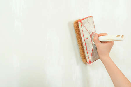 Painter worker is painting a wall with brush. Hand holding brush painting white color. Paint brush in hand, close up. Construction and renovation. Home renovations service. Banque d'images