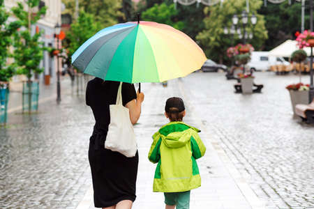 Summer day with rain. Happy family on a walk during rainy weather. Mother with big colorful rainbow umbrella. Rainy day in summertime. Family at city street.