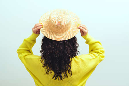 Brunette girl with long curly hair, back view. Beautiful woman wears summer hat. Beauty and fashion. Female with wavy hairstyle. Healthy lifestyle, wellness.