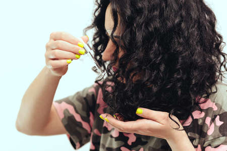 Woman applying natural oil on the tips of her curly hair, close up. Curly woman using serum for hair at home. Healthy curly hair. Natural products and cosmetics for hair. Banque d'images