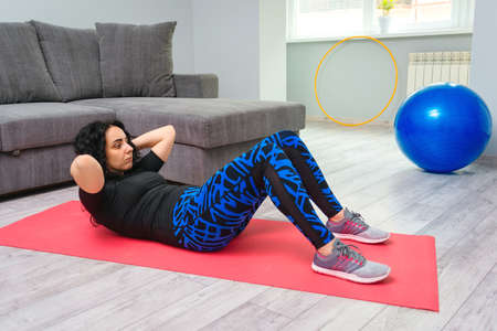 Young woman doing exercise on floor at home. Girl doing core crunches on mat. Fitness, home and diet concept. Woman training in living room during quarantine.