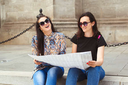 Young happy friends sightseeing in city. Friendship and travel concept. Two women reading map on the street. Fashionable girls walking in Europe modern city center. Travle, lifestyle, vacations.