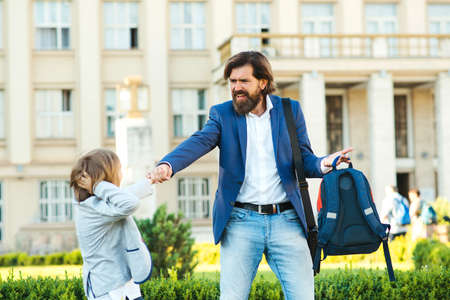 Schoolboy does not want to go to school. Father taking son to school. Dad hurries, is late to school and work. Child has tantrum before lessons. Parents, relationship with children and family problem.