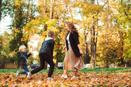 Mother with children throwing autumn leaves in a park. Autumn holidays. Mom and her sons having fun outdoors. Fashionable family walking in autumn nature. Family, fashion and lifestyle Stock Photo