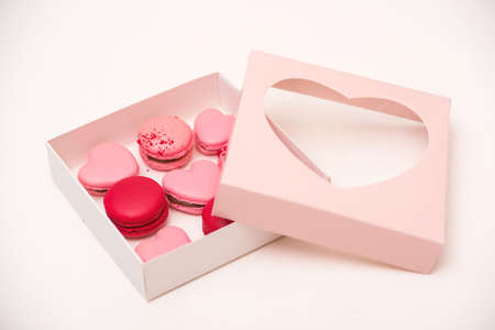 Macaroons cookies in box on white table. French cookies in gift box. Sweet macarons in gift box. Traditional french colorful macarons. Valentine's day gift. Pink macarons in the heart shape. Stock Photo