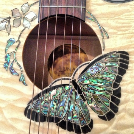 A luna guitar with butterfly decorations made out of shell