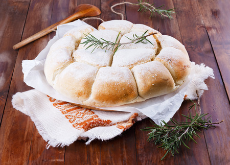 damper: Freshly baked Australian damper loaf with rosemary on a rustic cloth on wooden background