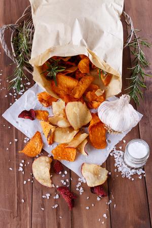 健康野菜のビート、サツマイモ、素朴な木製の背景のクローズ アップでニンニクとローズマリー海の塩と紙の上の白いさつまいもチップス