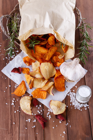 Healthy vegetable beetroot, sweet potato and white sweet potato chips on  paper with sea salt, rosemary and garlic on a rustic wooden background closeup