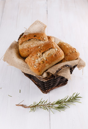 Ciabatta bread in a woven basket on a white wooden background photo