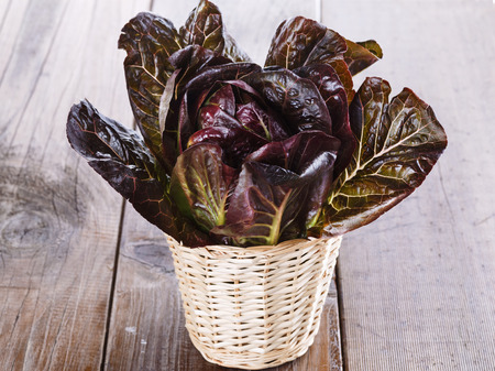 cos: Red cos lettuce on a woven basket over wooden background