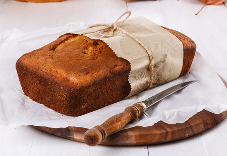 Pumpkin bread loaf on a chopping board over white wooden background Banco de Imagens