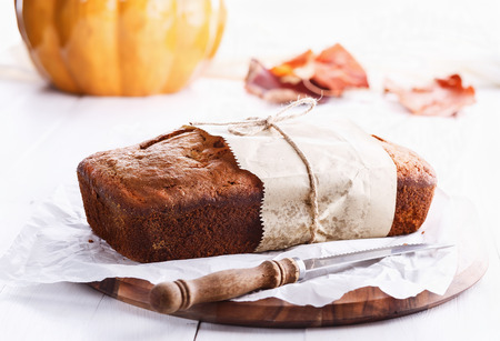 bread knife: Pumpkin bread loaf over white wooden background. Selective focus, shallow Depth of Field Stock Photo