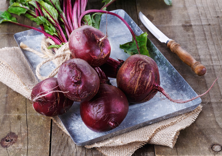 Bunch of organic beetroot on a vintage metal over rustic wooden background