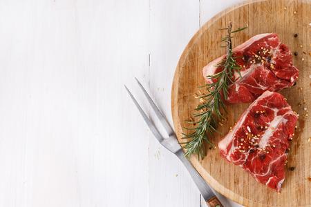 carne roja: Fondo con las carnes rojas y romero sobre la mesa de madera blanca. Vista superior Foto de archivo
