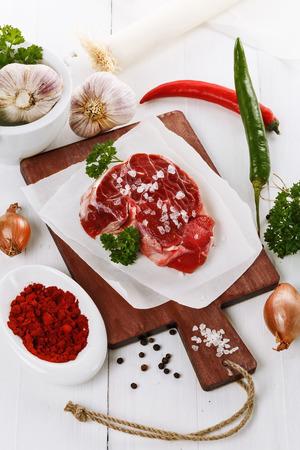 carne roja: La carne roja con hierbas y especies m�s de fondo blanco de madera