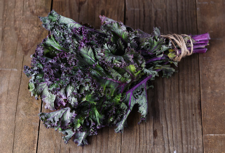 shallow dof: Bunch of organic kale on a rustic wooden background. Selective focus, shallow dof Stock Photo