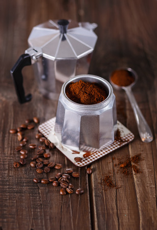 Ground coffee, coffee beans and Moka Pot coffee maker over rustic wooden background. Selective focus, shallow DoF Banco de Imagens