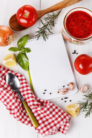Cooking concept. Recipe book and ingredients for cooking tomato soup over white wooden background. Top view photo