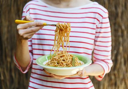 別のフォーク片手にスパゲッティとパスタのプレートを保持している女性 写真素材