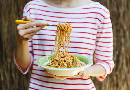 Female holding plate of spaghetti in one hand and spaghetti on fork with another photo