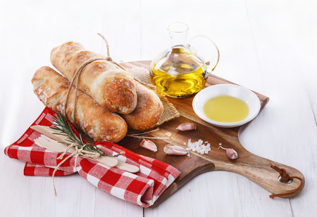 artisan bakery: Stone Baked Pane Di Casa bread rolls and aromatic oil on a white wooden background