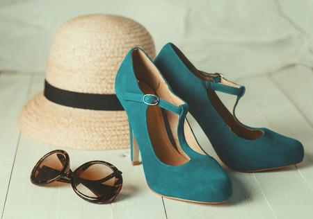 女性のファッションのレトロなスタイルのイメージ: 麦わら帽子、サングラスと白い木製の背景に青緑色の靴。選択と集中、浅い被写し界深度、ビン
