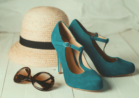 shoes fashion: Retro style image of female fashion: straw hat, sun glasses and turquoise shoes over white wooden background. Selective focus, shallow DoF, vintage filters Stock Photo