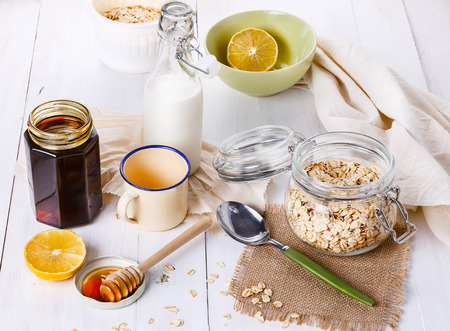 healthy living: Breakfast with rolled oat, honey and milk over white wooden