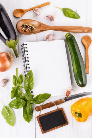 Cooking concept. Recipe book and ingredients for cooking vegetables over white wooden  photo