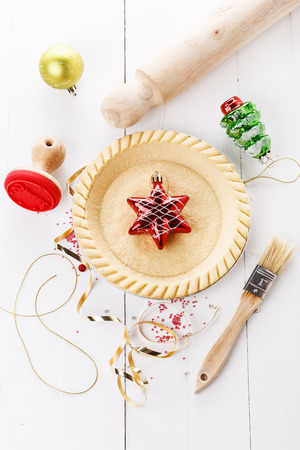 Charismas baking concept. Tart base and utensils over white wooden background. Top view photo