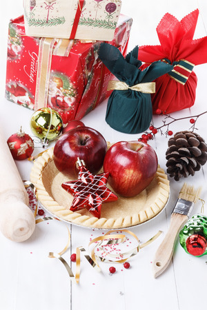 Charismas baking concept. Tart base, utensils, apples and Christmas ornaments over white wooden background. Selective focus photo