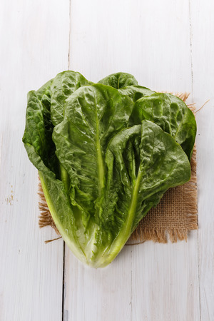 cos: Cos lettuce on burlap cloth on a white wooden background Stock Photo