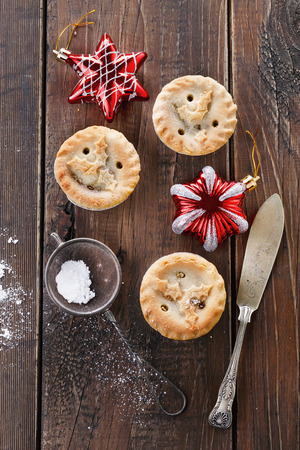 Christmas fruit mince pies and Christmas ornaments over rustic wooden background. Top view photo