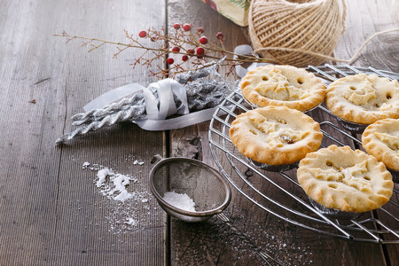 Pile of Christmas fruit mince pies and Christmas decorations over rustic wooden background