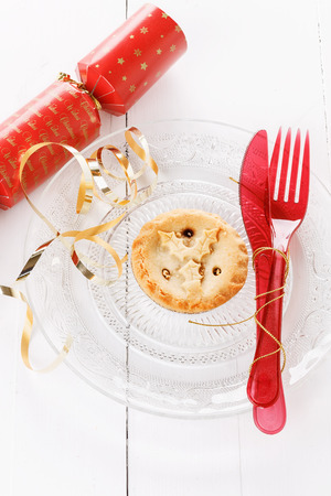 Single Christmas fruit mince pie in a crystal plate and red Christmas tableware over rustic wooden background