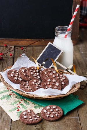 Chocolate Christmas cookies on a woven plate with tag and bottle of milk over rustic wooden background photo