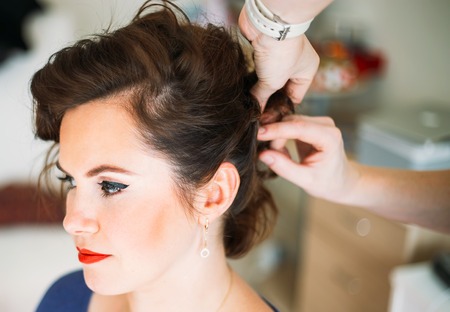 Hairdresser hands doing hair for a beautiful lady with classic make up. Selective focus, shallow Depth of Field photo