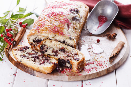Sliced cranberry loaf on a wooden tray over white wooden background, close up photo