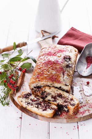 Sliced cranberry loaf on a wooden tray over white wooden background photo