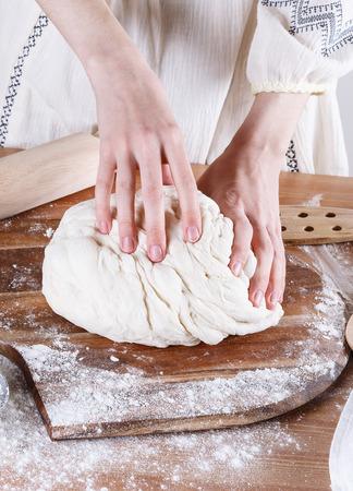 Baker hands making sourdough bread on a wooden table Banco de Imagens