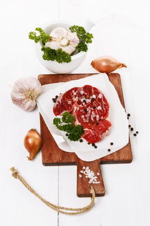 carne roja: La carne roja con ajo, cebolla y perejil sobre fondo de madera blanca Foto de archivo
