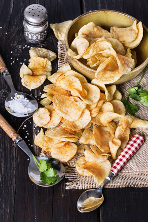 Pile of homemade potato chips over dark wooden background photo