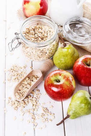 rolled oats: Fresh apples and pears and rolled oats over white wooden background. Selective focus, shallow DoF