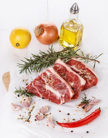 carnes rojas: Red de carne, verduras y especias sobre fondo de madera blanca