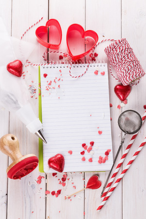 kitchen tool: Valentine day baking concept with heart shaped cookie cutters, chocolate hearts and kitchen tool. Top view, Copy space