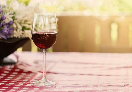 自然の背景にぼんやりとした日光、ボケ味の赤ワインの 1 つのガラス。コピー領域、選択と集中、浅い被写し界深度 写真素材
